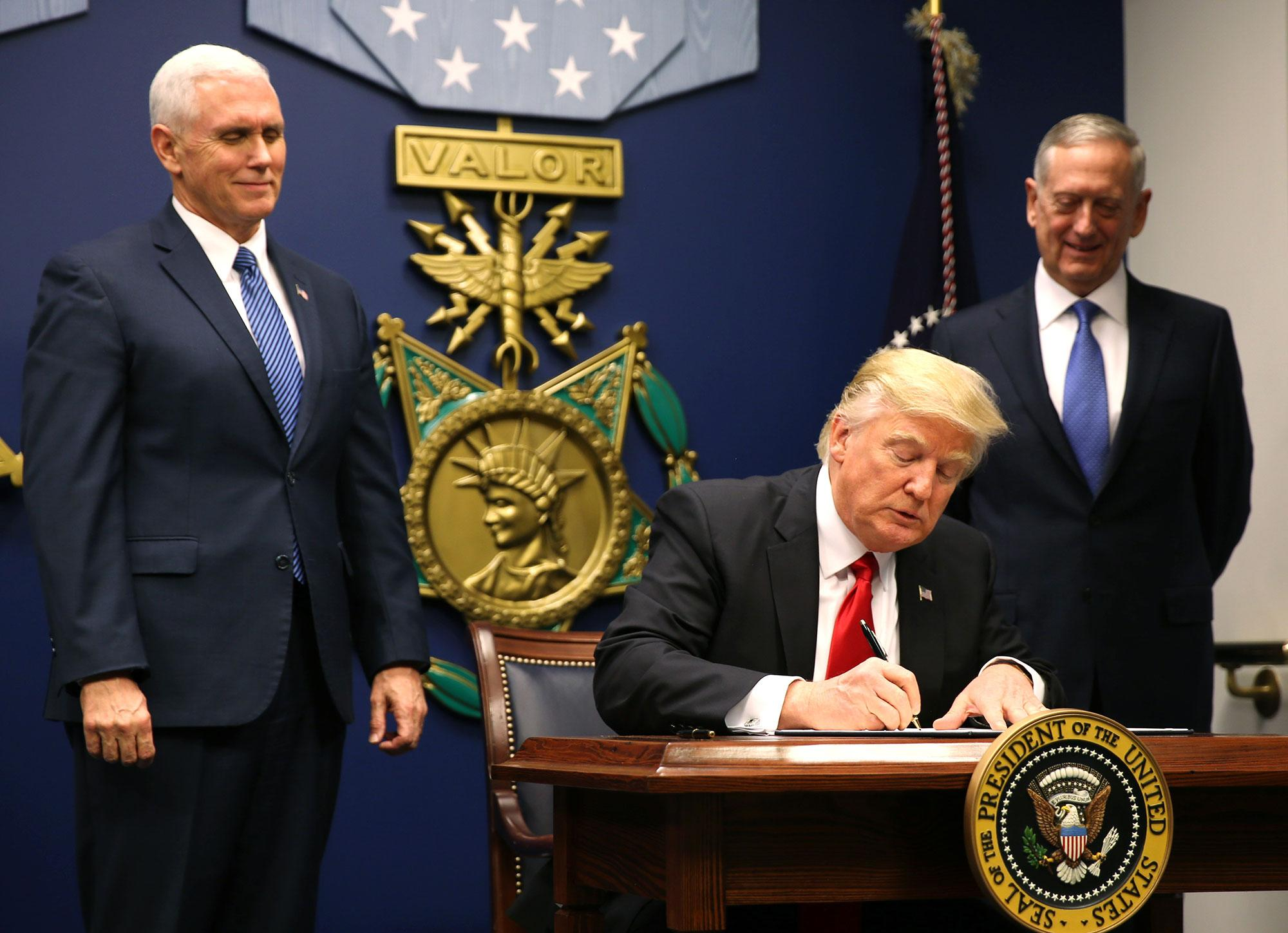 <p>President Donald Trump (C) signs an Executive Order establising extreme vetting of people coming to the United States after attending a swearing-in ceremony for Defense Secretary James Mattis (R) with Vice President Mike Pence at the Pentagon in Washington, U.S., January 27, 2017. The executive order signed by Trump imposes a four-month travel ban on refugees entering the United States and a 90-day hold on travelers from Syria, Iran and five other Muslim-majority countries. (Carlos Barria/Reuters) </p>