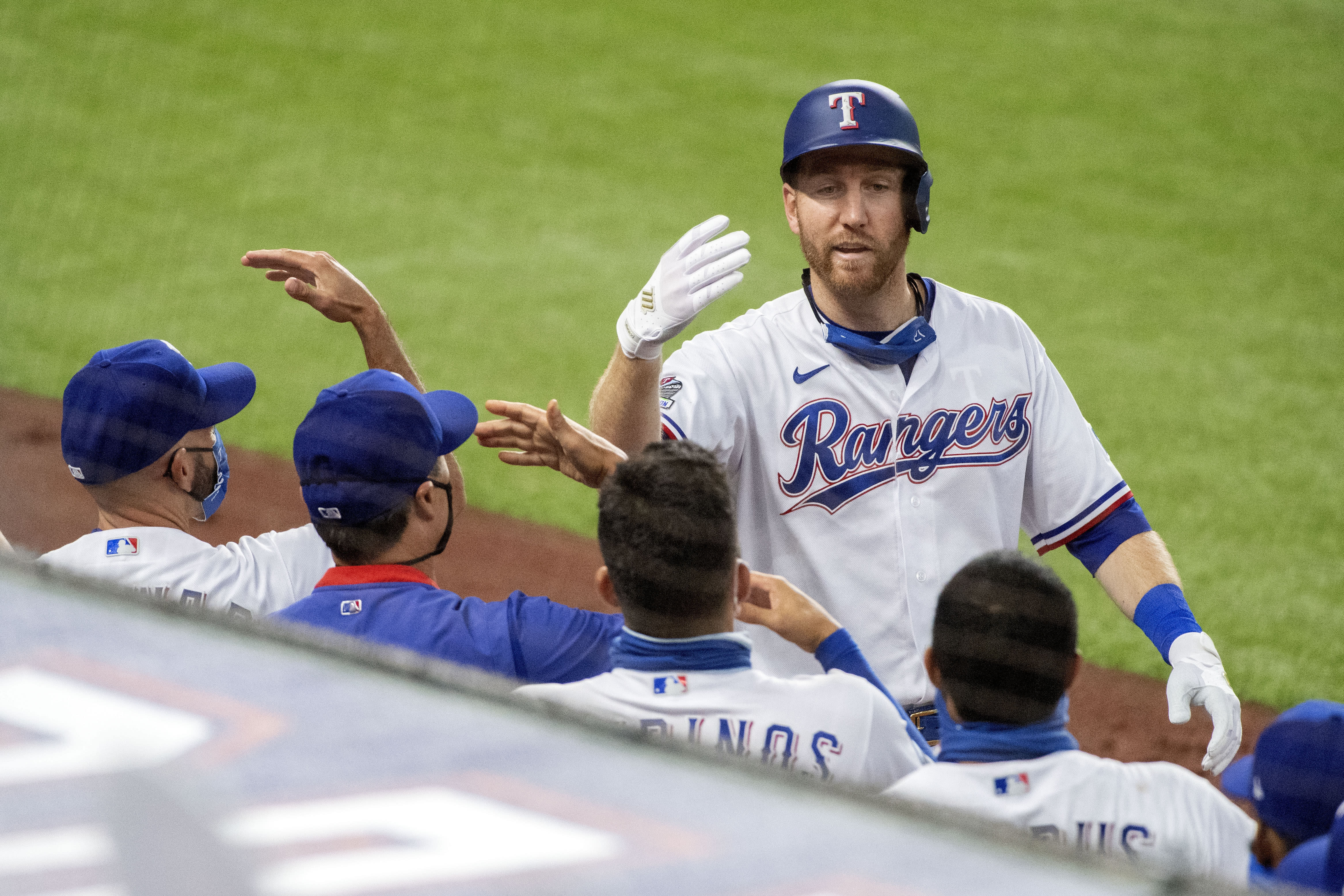 Texas Rangers' Todd Frazier celebrates with teammates after his solo home run off of Arizona Diamondbacks starting pitcher Madison Bumgarner during the fourth inning of a baseball game Wednesday, July 29, 2020, in Arlington, Texas. (AP Photo/Jeffrey McWhorter)