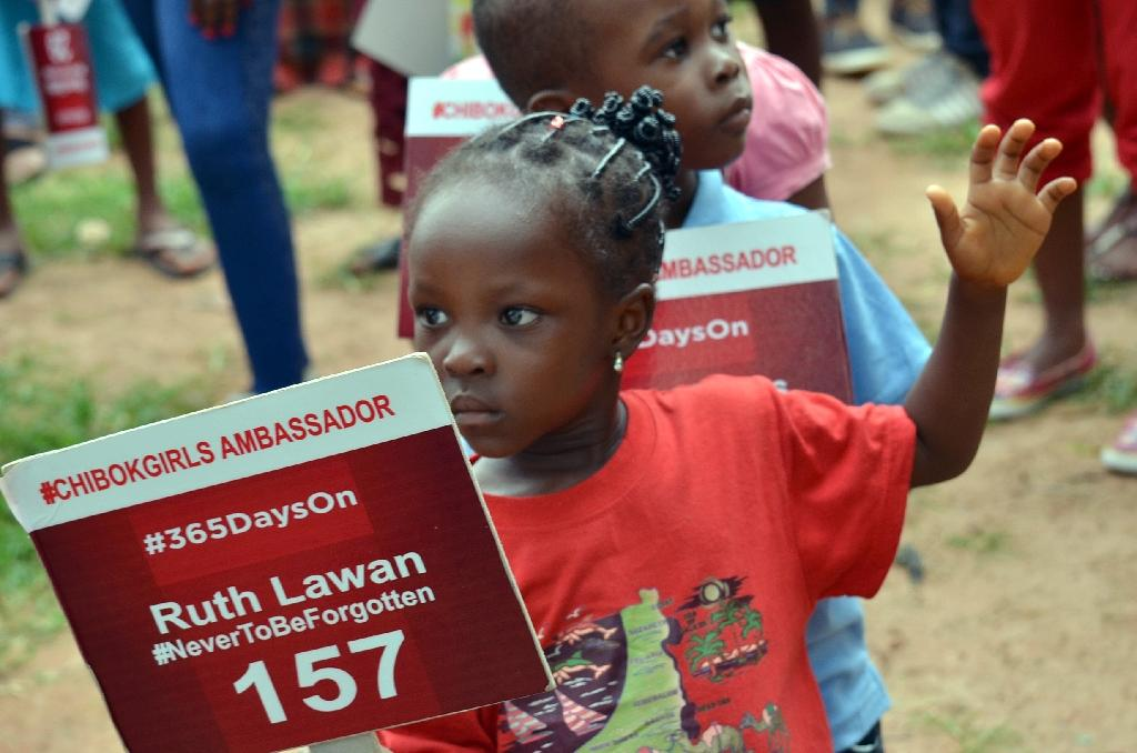 A young girl carries a sign with a name of a girl as family and friends mark 500 days since the abductions of the Chibok schoolgirls by Boko Haram, during a rally to press for their release in Abuja, on August 27, 2015 (AFP Photo/)