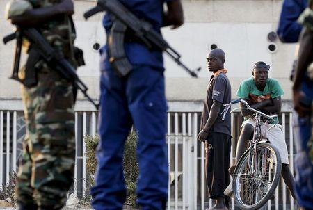 Residents look on as police and soldiers guard a voting station in Burundi's capital Bujumbura during the country's presidential election