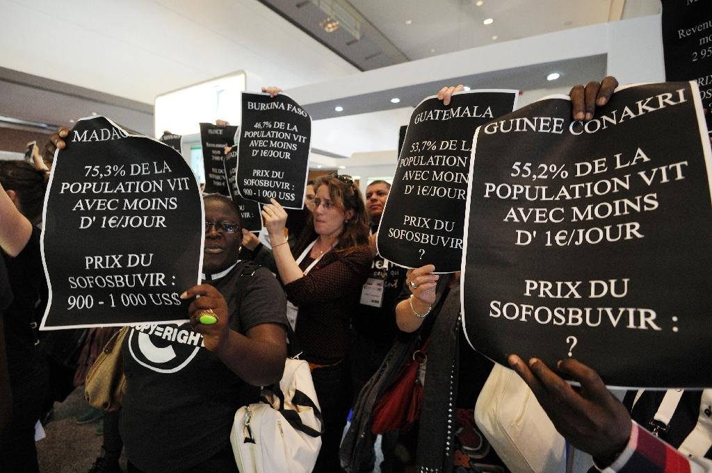 Members of the association Act Up hold signs in front of a stand of US pharmaceutical giant Gilead Sciences to denounce the high price of a new drug, Sofosbuvir, to treat Hepatitis C, on April 29, 2014 in Montpellier, southern France