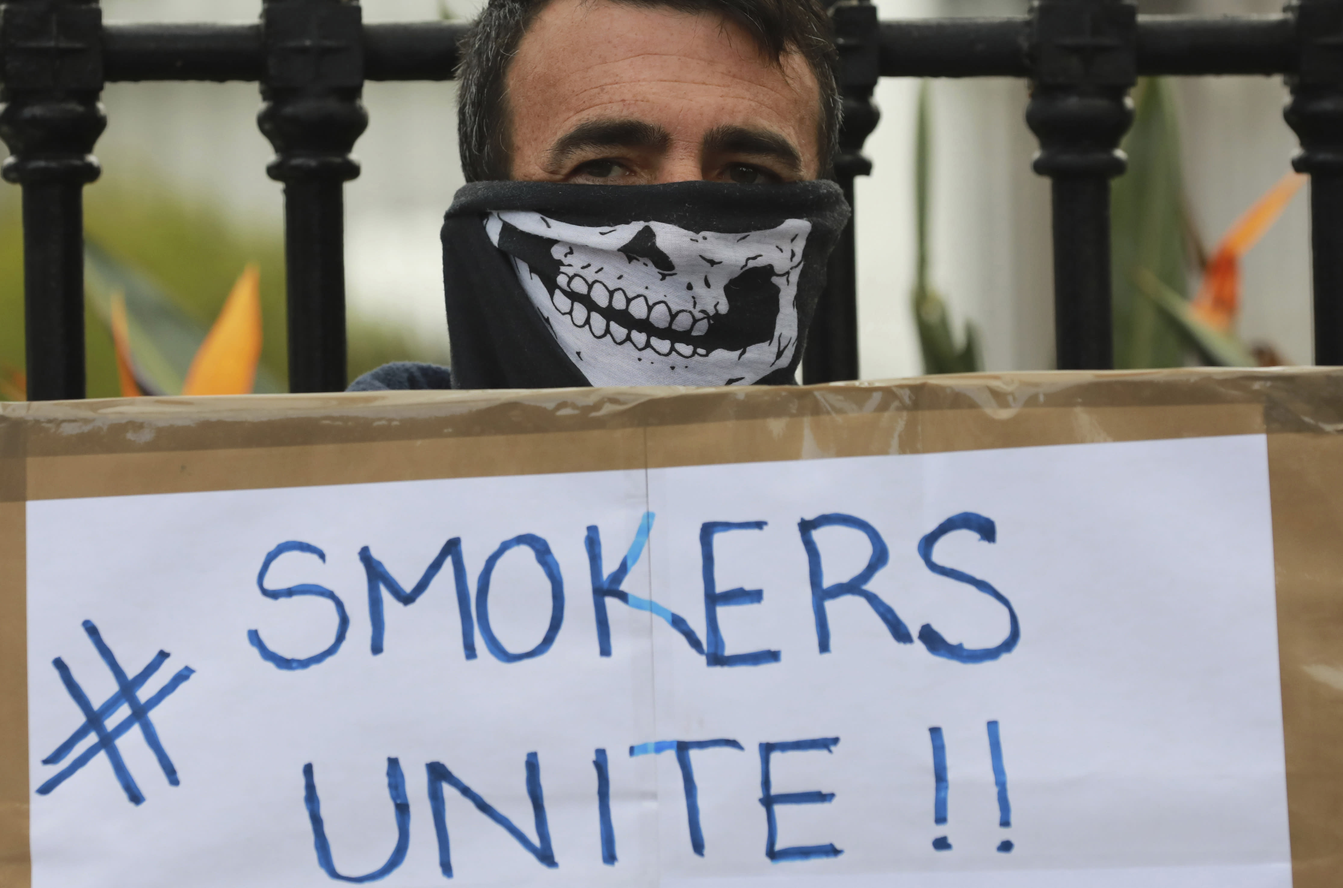 FILE — In this June 2, 2020 file photo, a demonstrator holds a placard during a protest against the tobacco ban outside parliament in Cape Town, South Africa. South Africa is three months into a ban on the sale of cigarettes and other tobacco products, an unusual tactic employed by a government to protect the health of its citizens during the coronavirus pandemic. The country is one of just a few around the world to have banned tobacco sales during the pandemic and the only one to still have it in place. (AP Photo/Nardus Engelbrecht/File)