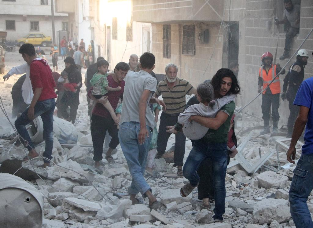 Men carry injured people through the rubble of destroyed buildings following a reported air strike on the rebel-held northwestern Syrian city of Idlib on September 29, 2016