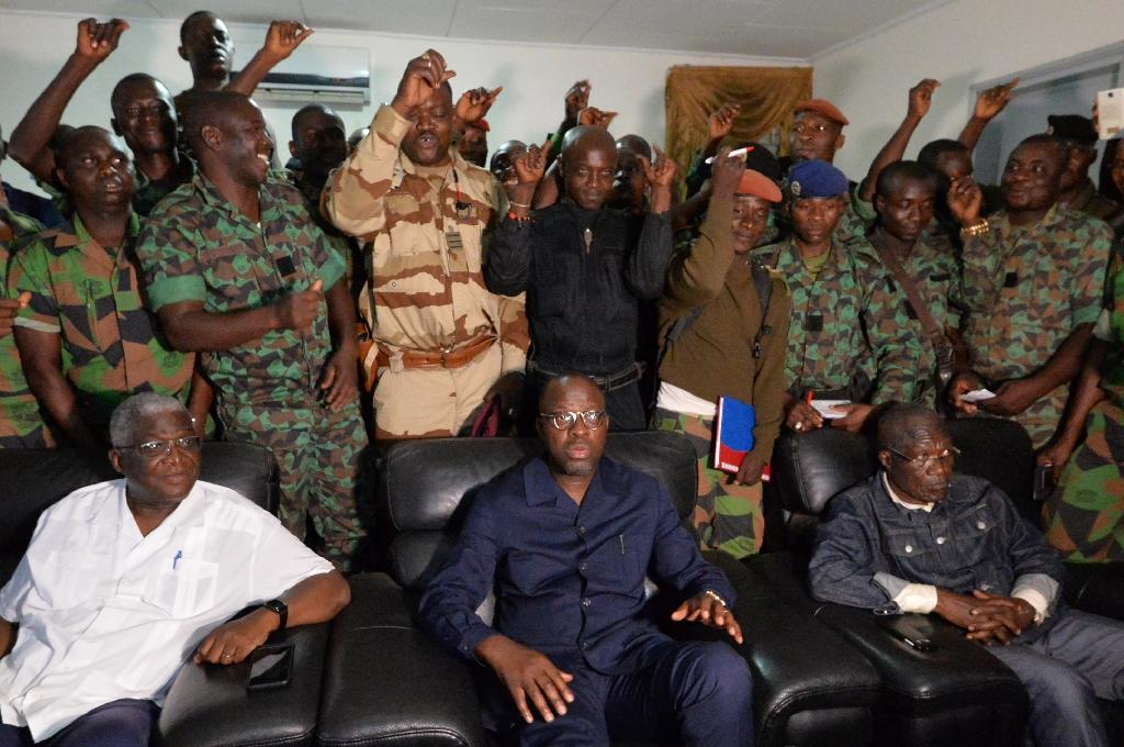 A delegation of mutinous Ivorian soldiers stand behind Defence Minister Alain-Richard Donwahi (C) as he speaks to journalists in Bouake, on January 7, 2017 (AFP Photo/SIA KAMBOU)
