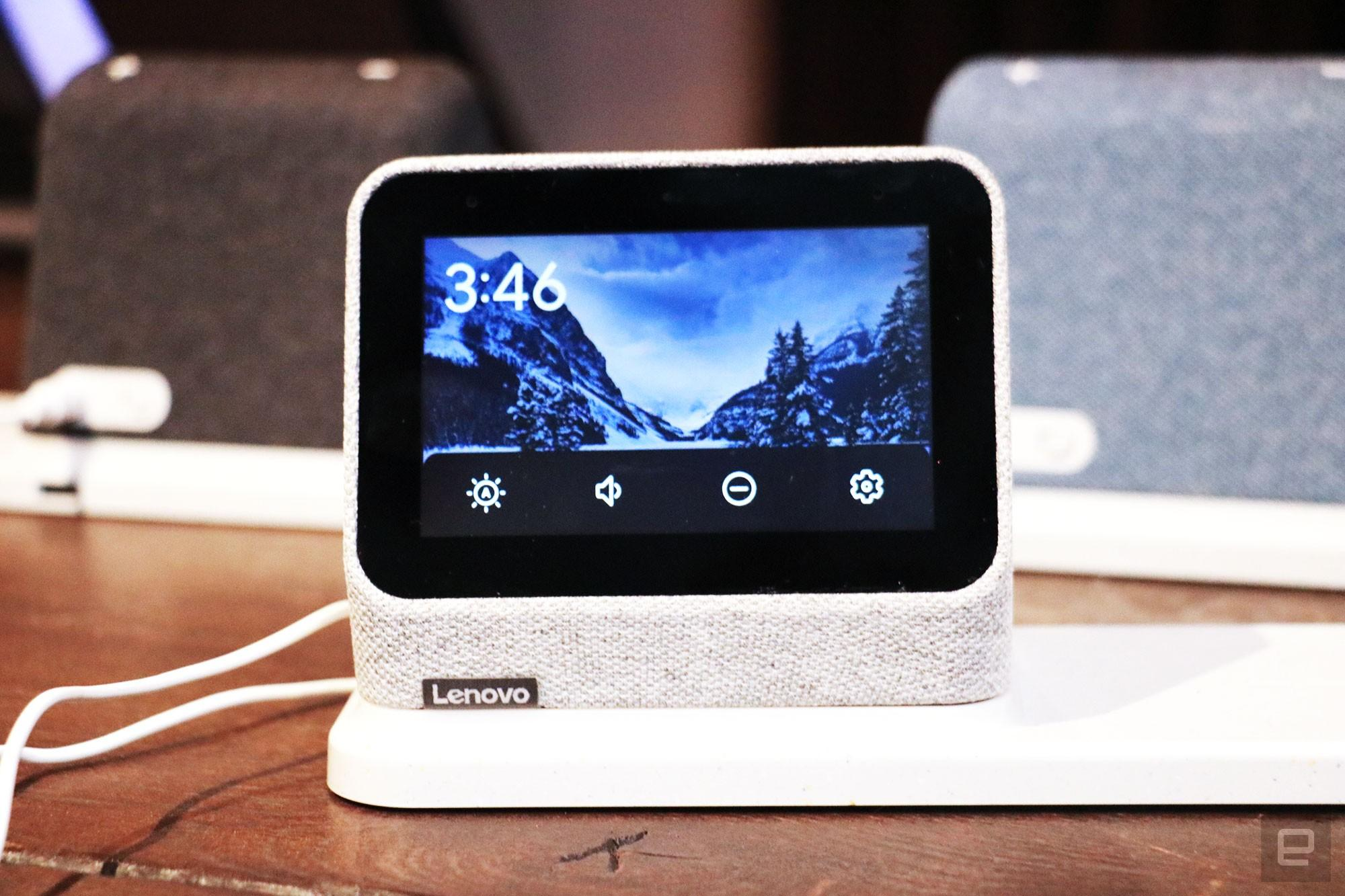 A gray Lenovo Smart Clock 2 on a wireless charging dock with its screen facing the camera. A row of options for volume, brightness, do not disturb and settings take up the bottom of the display.  In the background are a black and a blue Smart Clock 2 on the left and right respectively.