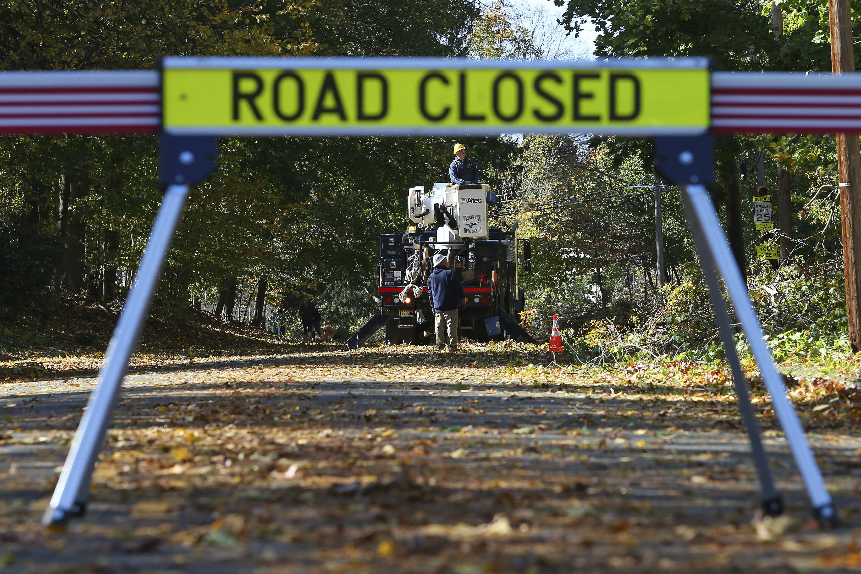 Crews from Butler Municipal Power and Light work on downed power lines on Green Village Road, Friday, Nov. 1, 2019, in Madison, N.J. The borough was hit by high winds on heavy rain late the night before. (AP Photo/Rich Schultz)