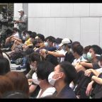 Hong Kong protesters corralled and made to sit down by riot police during rally against national anthem bill