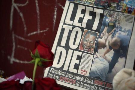 A picture of Eric Garner is seen on a newspaper at his memorial in Staten Island, New York, July 21, 2014. REUTERS/Eduardo Munoz