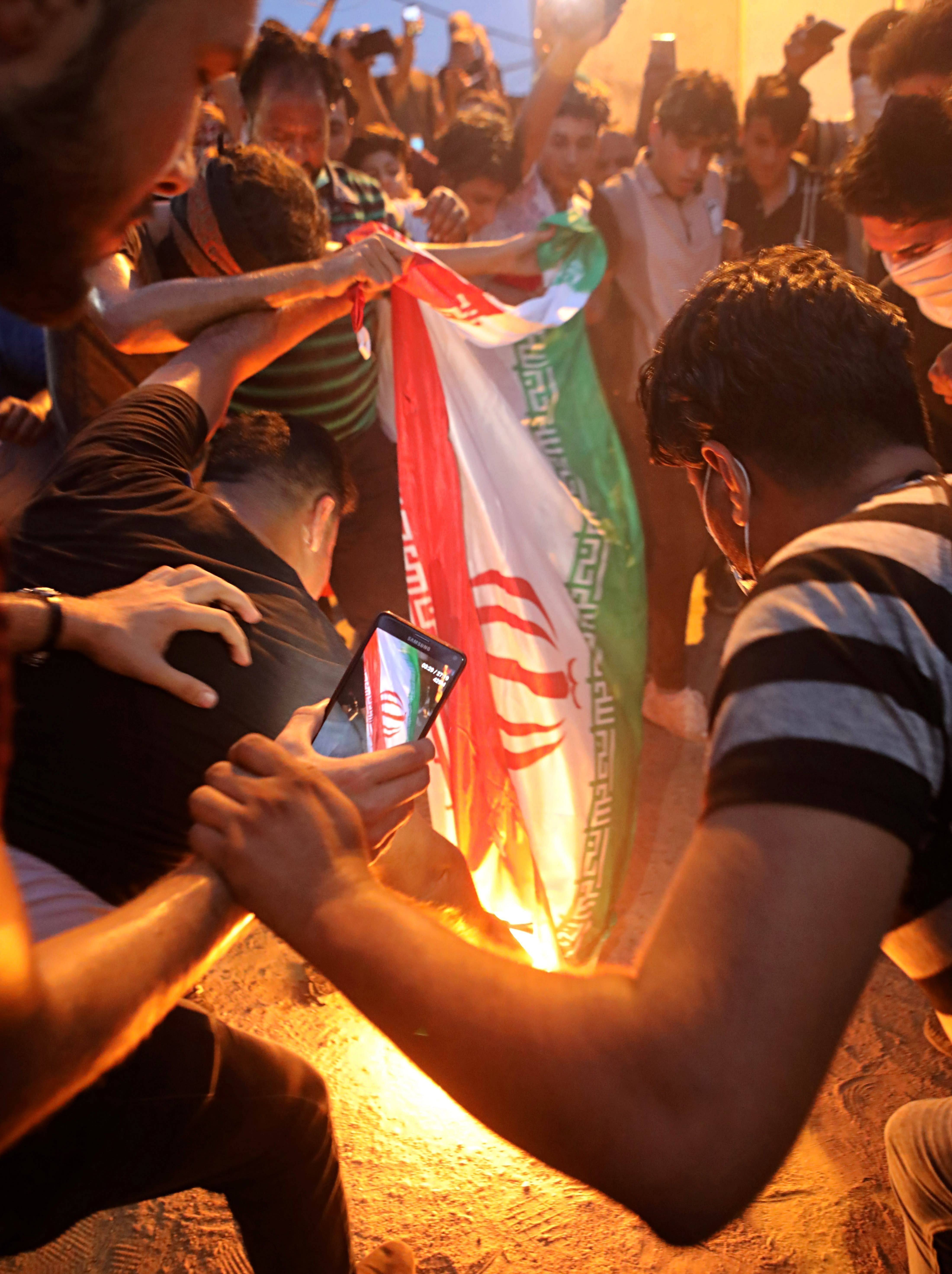 FILE - In this Friday, Sept. 7, 2018 file photo, protesters burn an Iranian flag after storming and burning the Iranian consulate building in Basra, Iraq. A falsely captioned version of this photo began circulating on social media as protests escalated in Iraq in early October 2019, incorrectly claiming that it shows protesters burning an Iranian flag in Baghdad as Iraqis held anti-government protests around the country. (AP Photo/Nabil al-Jurani, File)
