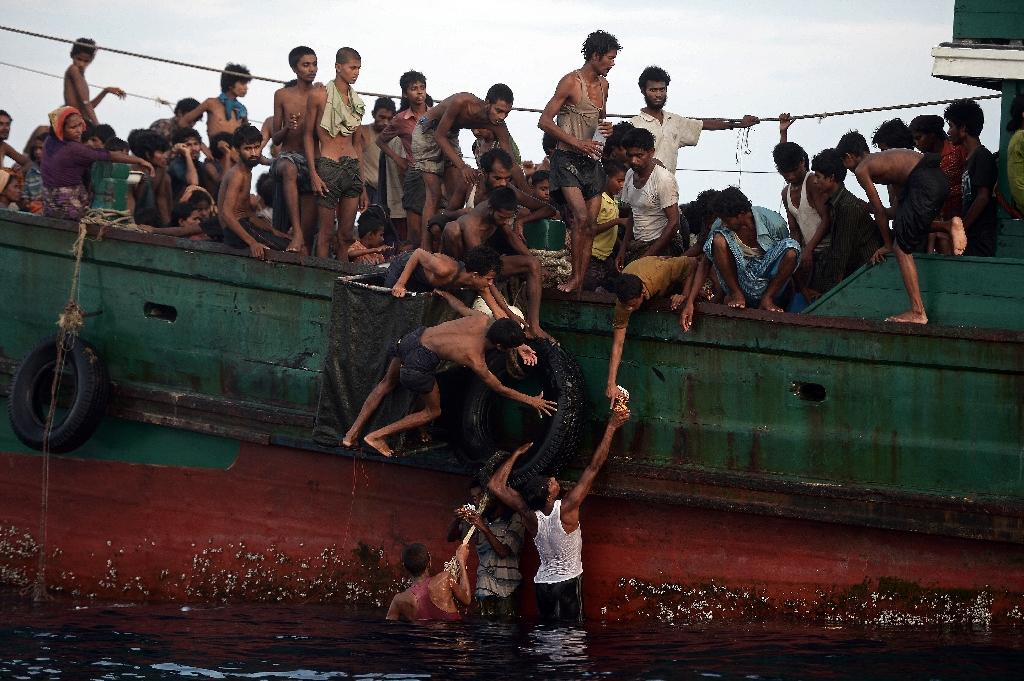 Rohingya migrants pass food supplies dropped by a Thai army helicopter to others aboard a boat drifting in Thai waters off the southern island of Koh Lipe in the Andaman sea on May 14, 2015 (AFP Photo/Christophe Archambault)
