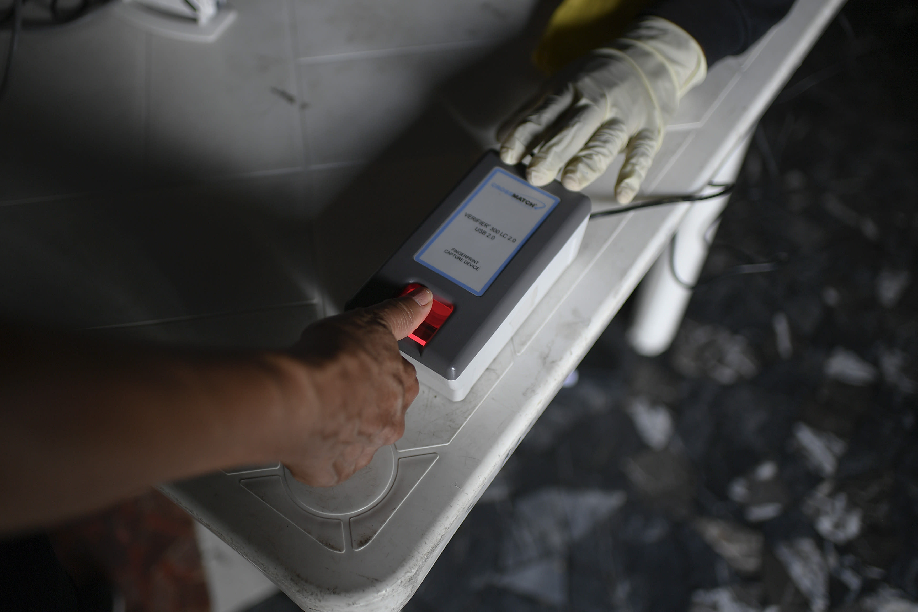 A woman places her thumb on a handheld fingerprint scanner at a validation center to certify the authenticity of voter data in Caracas, Venezuela, Saturday, July 25, 2020, amid the new coronavirus pandemic. The legislative election is scheduled for Dec. 6 and thus far the opposition has indicated it will not participate. (AP Photo/Matias Delacroix)