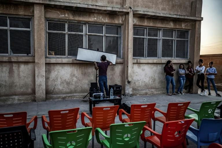 Shero Hinde uses just a laptop, projector and a canvas screen to show films in remote northeastern Syrian villages (AFP Photo/DELIL SOULEIMAN)