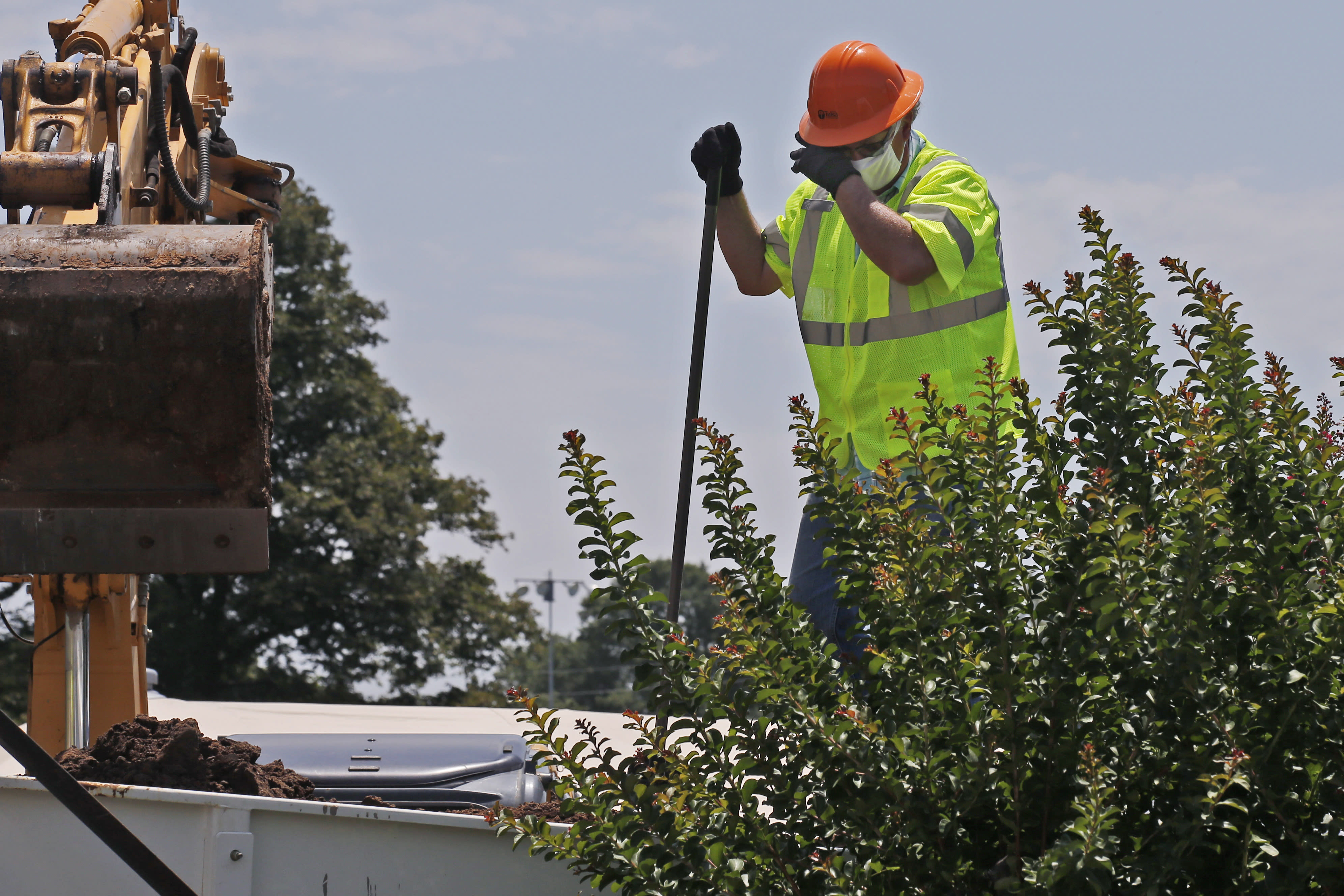 A worker pauses to wipe his face in the heat as work continues on an excavation of a potential unmarked mass grave from the 1921 Tulsa Race Massacre, at Oaklawn Cemetery in Tulsa, Okla., Tuesday, July 14, 2020. On May 31 and June 1 in 1921, white residents looted and burned Tulsa's black Greenwood district, killing as many as 300 people with many believed buried in mass graves. (AP Photo/Sue Ogrocki)