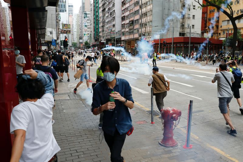 Anti-government protesters react as riot police fire tear gas to disperse them during a march against Beijing's plans to impose national security legislation in Hong Kong