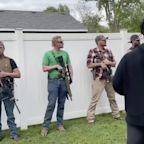 Group carrying guns watch Floyd protesters march in Indiana