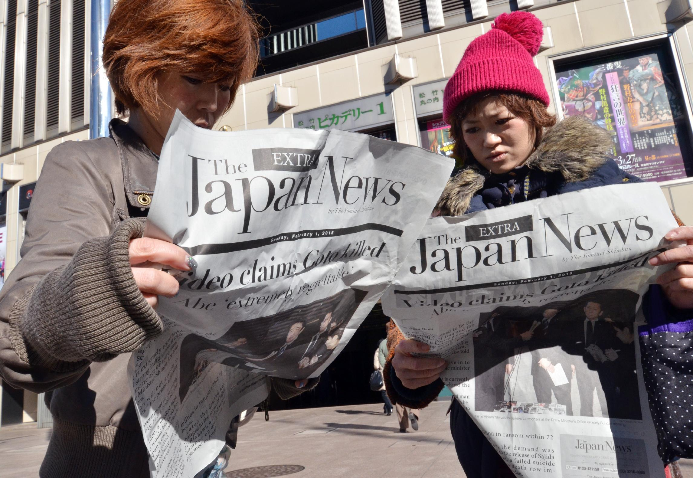Two women read an extra edition newspaper reporting the killing of Japanese hostage Kenji Goto in Tokyo on February 1, 2015 (AFP Photo/Yoshikazu Tsuno)