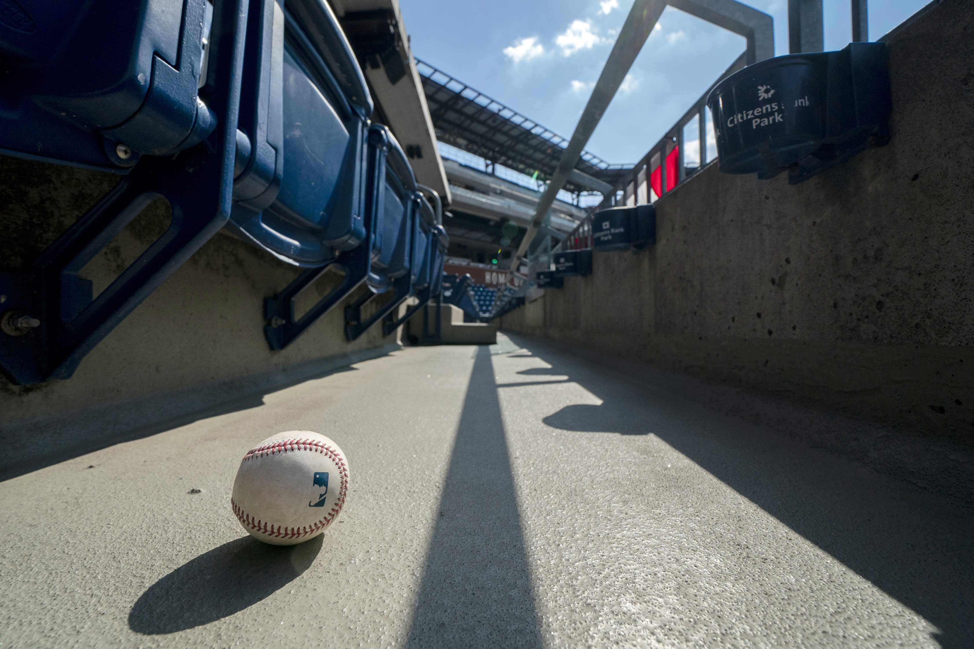 FILE - In this Sunday, July 26, 2020, file photo, a foul ball that was hit into the stands sits on the ground of an empty stadium during the eighth inning of a baseball game between the Miami Marlins and the Philadelphia Phillies in Philadelphia. The Marlins' coronavirus outbreak could endanger the Major League Baseball season, Dr. Anthony Fauci said, as the number of their players testing positive rose to 15. The Marlins received positive test results for four additional players Tuesday, July 23, 2020, a person familiar with the situation told The Associated Press. The person declined to be identified because the results had not been publicly released. (AP Photo/Chris Szagola, File)
