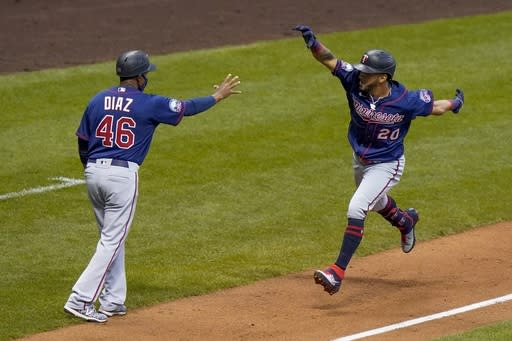 Minnesota Twins' Eddie Rosario celebrates his grand slam with third base coach Tony Diaz during the third inning of a baseball game against the Milwaukee Brewers Monday, Aug. 10, 2020, in Milwaukee. (AP Photo/Morry Gash)
