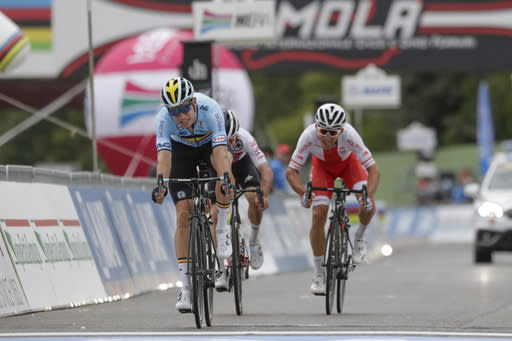 Belgium's Wout van Aert sprints ahead of Switzerland's Marc Hirschi and Poland's Michal Kwiatkowski, right, to clinch the silver medal in the men's elite event, at the road cycling World Championships, in Imola, Italy, Sunday, Sept. 27, 2020. (AP Photo/Andrew Medichini)