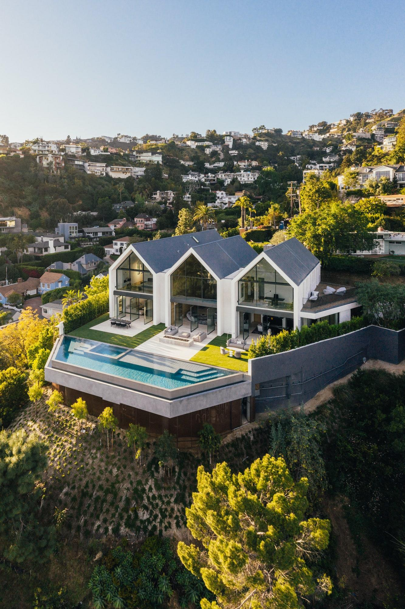 """""""We kept the exterior materials simple: white plaster and zinc-color metal roofing,"""" says Jeffrey Allsbrook of Standard Architecture. The architects also built the home on a perch along the side of a hill, allowing for more space to be used off the back patio."""