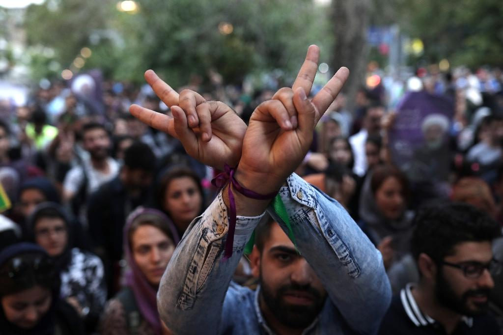 A supporter of newly re-elected Iranian President Hassan Rouhani flashes the sign for victory as he takes to the streets to celebrate his victory in downtown Tehran on May 20, 2017 (AFP Photo/Behrouz MEHRI)