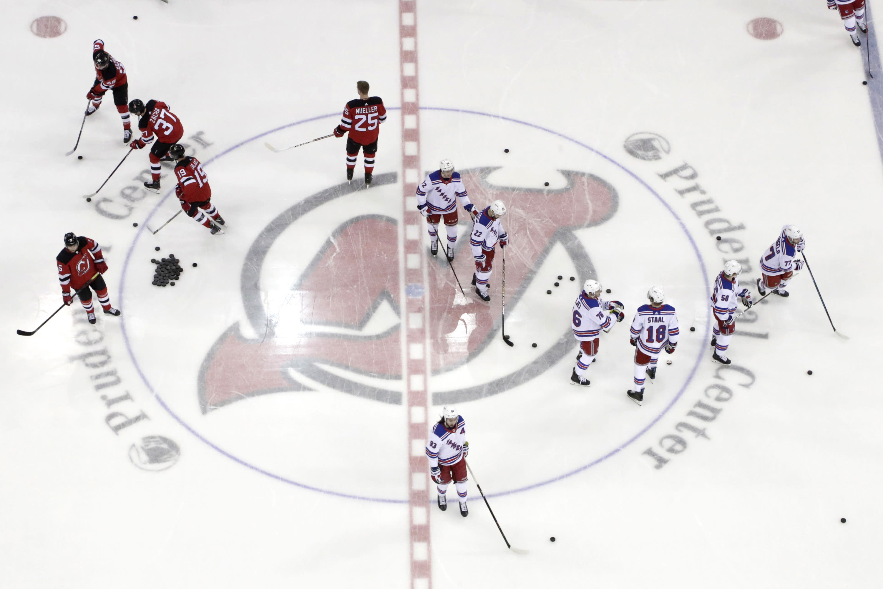 FILE - In this April 1, 2019, file photo, New Jersey Devils, left, and New York Rangers warm up for an NHL hockey game in Newark, N.J. Deputy Commissioner Bill Daly told The Associated Press on Sunday, July 5, 2020, that the NHL and NHL Players' Association have agreed on protocols to resume the season. Daly said the sides are still negotiating a collective bargaining agreement extension. A CBA extension is still crucial to the process. (AP Photo/Julio Cortez, File)