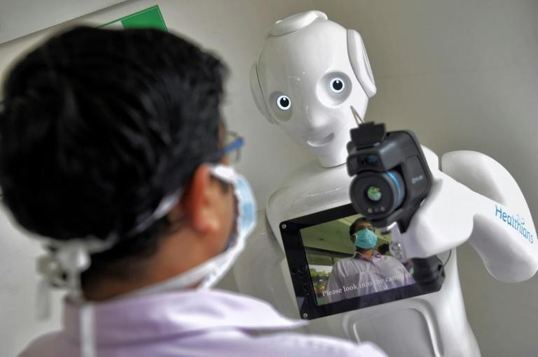 Robots are stepping into the breach during the coronavirus crisis, but what does this mean for jobs? (AFP Photo/Manjunath Kiran)