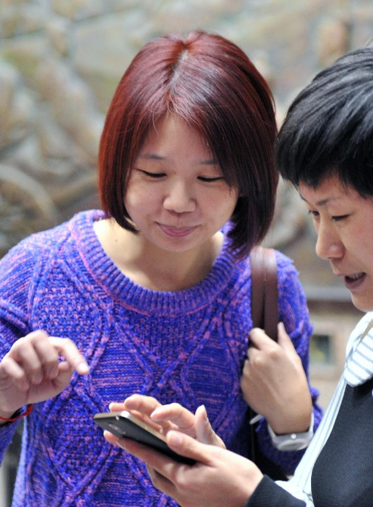 Lin Li-chan (L) speaks with her friend after a meeting at the Education Ministry in Taipei (AFP Photo/Sam Yeh)