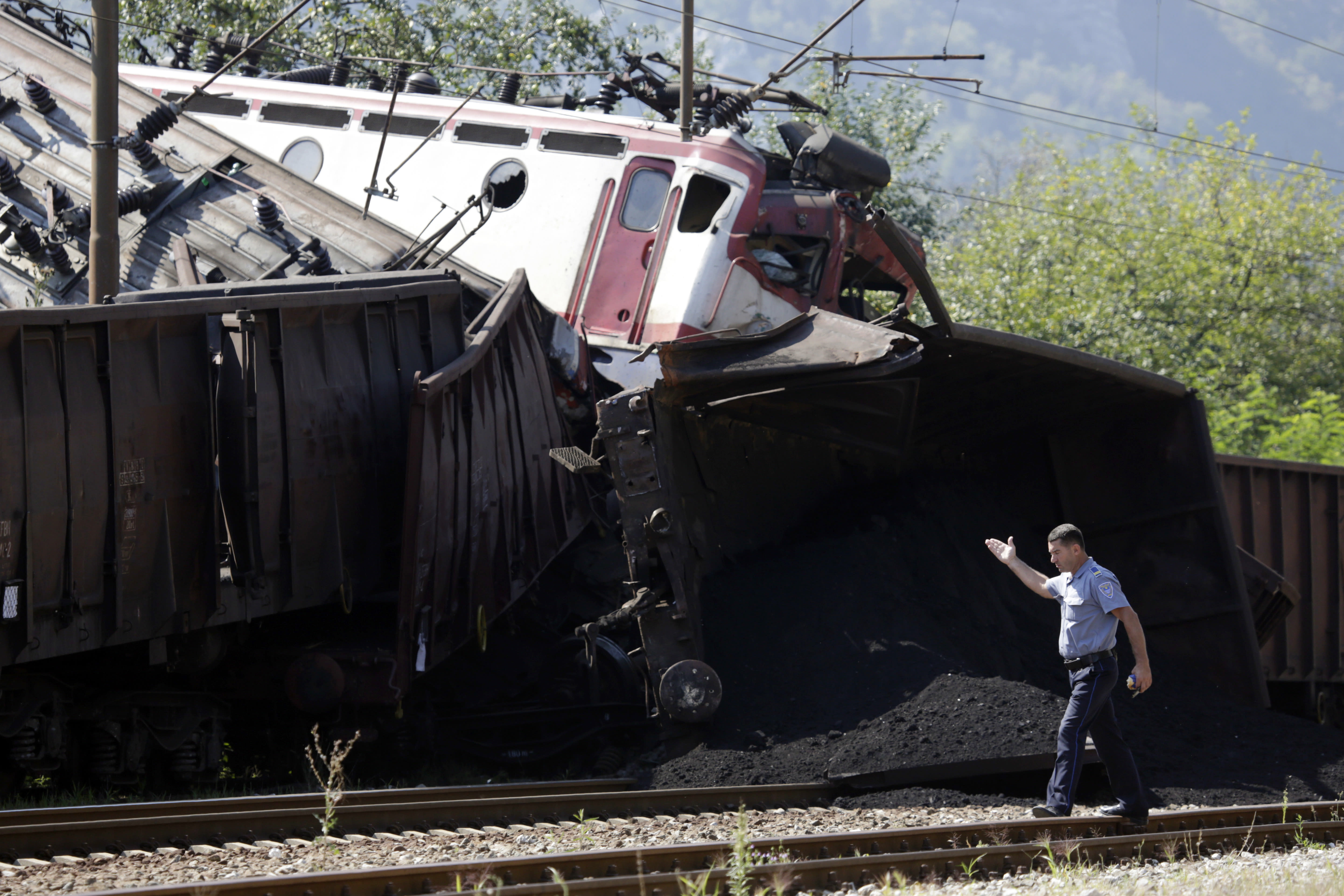 A police officer walks near the site where two cargo trains collided at the train station in Jablanica, about 80 kms south of Sarajevo, Bosnia, Thursday, Aug. 23, 2018. Police say two people have been killed and one was seriously injured in a head-on freight train collision in southern Bosnia, early Thursday.(AP Photo/Amel Emric)