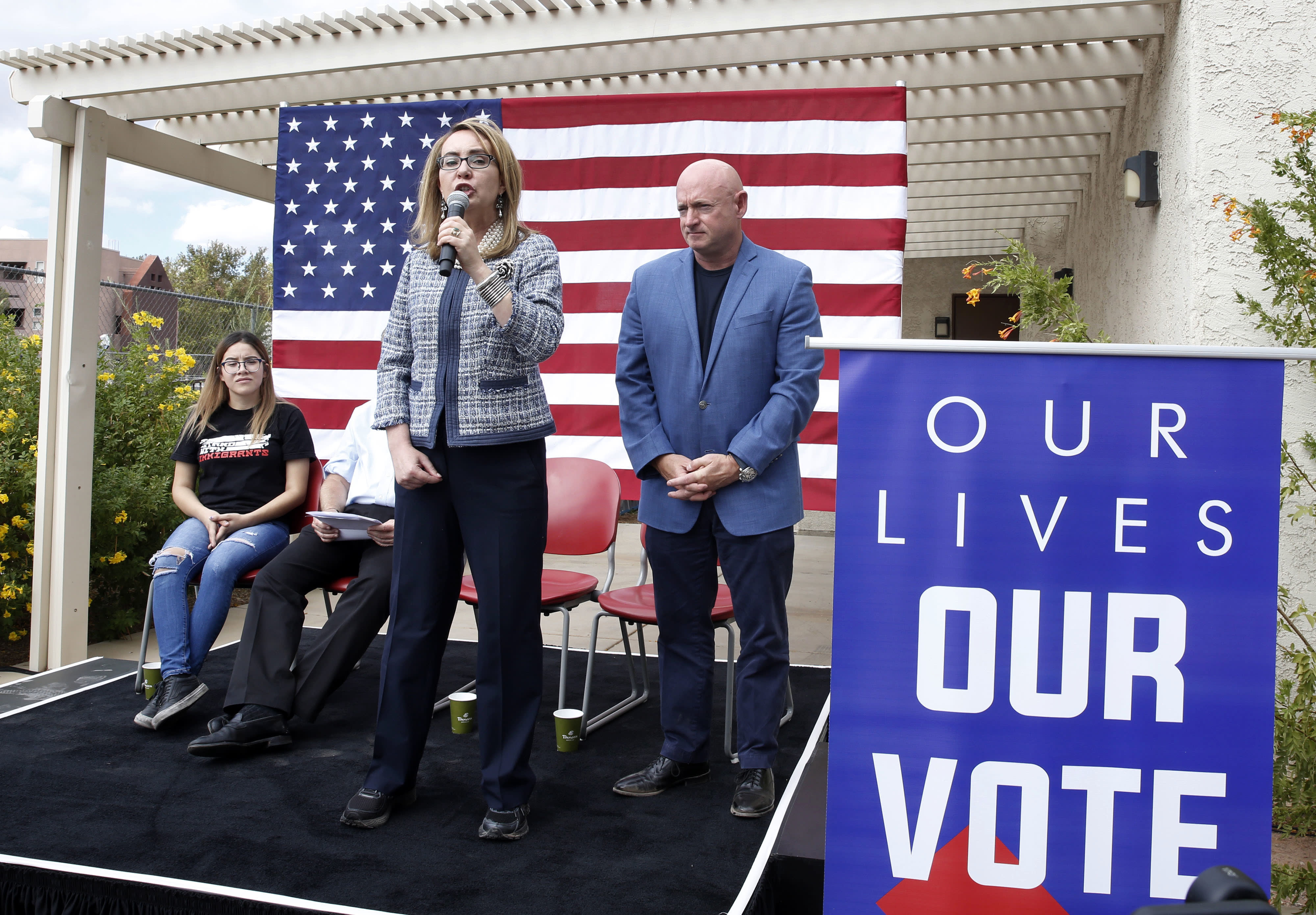 "In this Oct. 2, 2018 photo, former Rep. Gabby Giffords speaks as her husband, retired NASA astronaut and Navy Capt. Mark Kelly looks on as they kick off ""The Vote Save Lives"" tour at UNLV in Las Vegas. The 2018 election marks the first time that groups supporting gun control measures could spend more on a campaign than the National Rifle Association. (Bizuayehu Tesfaye/Las Vegas Review-Journal via AP)/Las Vegas Review-Journal via AP)"