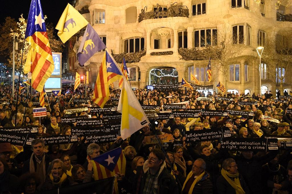 """People hold placards reading """"Self determination is a right, not a crime"""" in Barcelona on February 1, during a demonstration in support of jailed Catalan pro-independence leaders (AFP Photo/LLUIS GENE)"""
