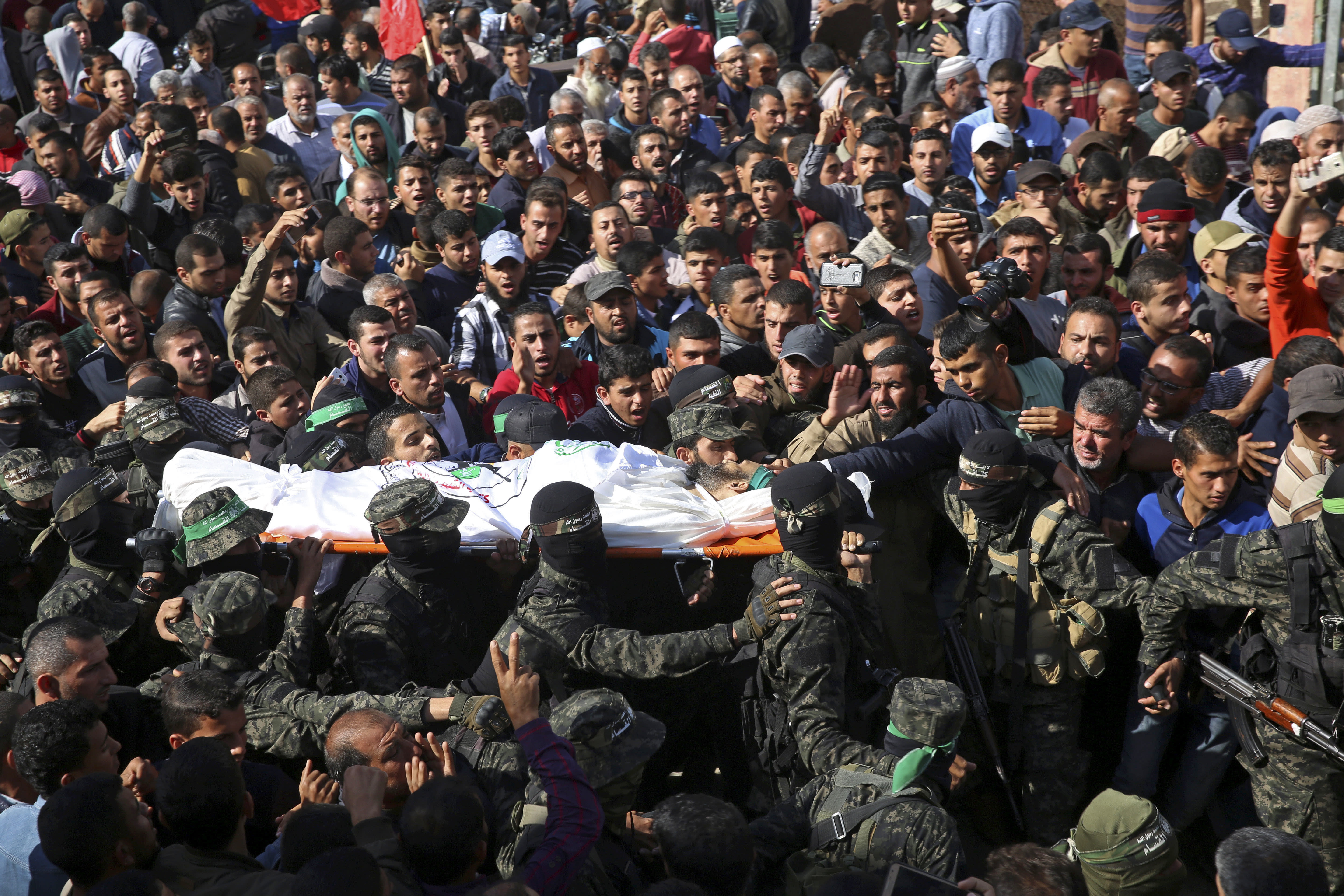 FILE - In this Monday, Nov. 12, 2018 file photo, mourners carry the body of Hamas militant commander Nour Baraka, who was killed during an Israeli raid late Sunday, during his funeral, at his family house in Khan Younis, southern Gaza Strip. A month after a heavy round of Israel-Hamas fighting, the undercover Israeli operation that sparked the battle remains clouded in mystery.(AP Photo/Adel Hana, File)