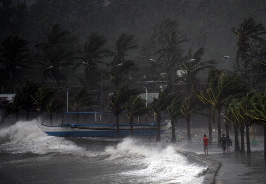 Residents walk past high waves brought about by strong winds, hours before Typhoon Hagupit passes near the city of Legazpi on December 7, 2014 (AFP Photo/Ted Aljibe)
