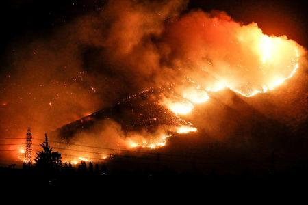Fire is seen on a hill in a town called Pirque, on the outskirts of Santiago, Chile.