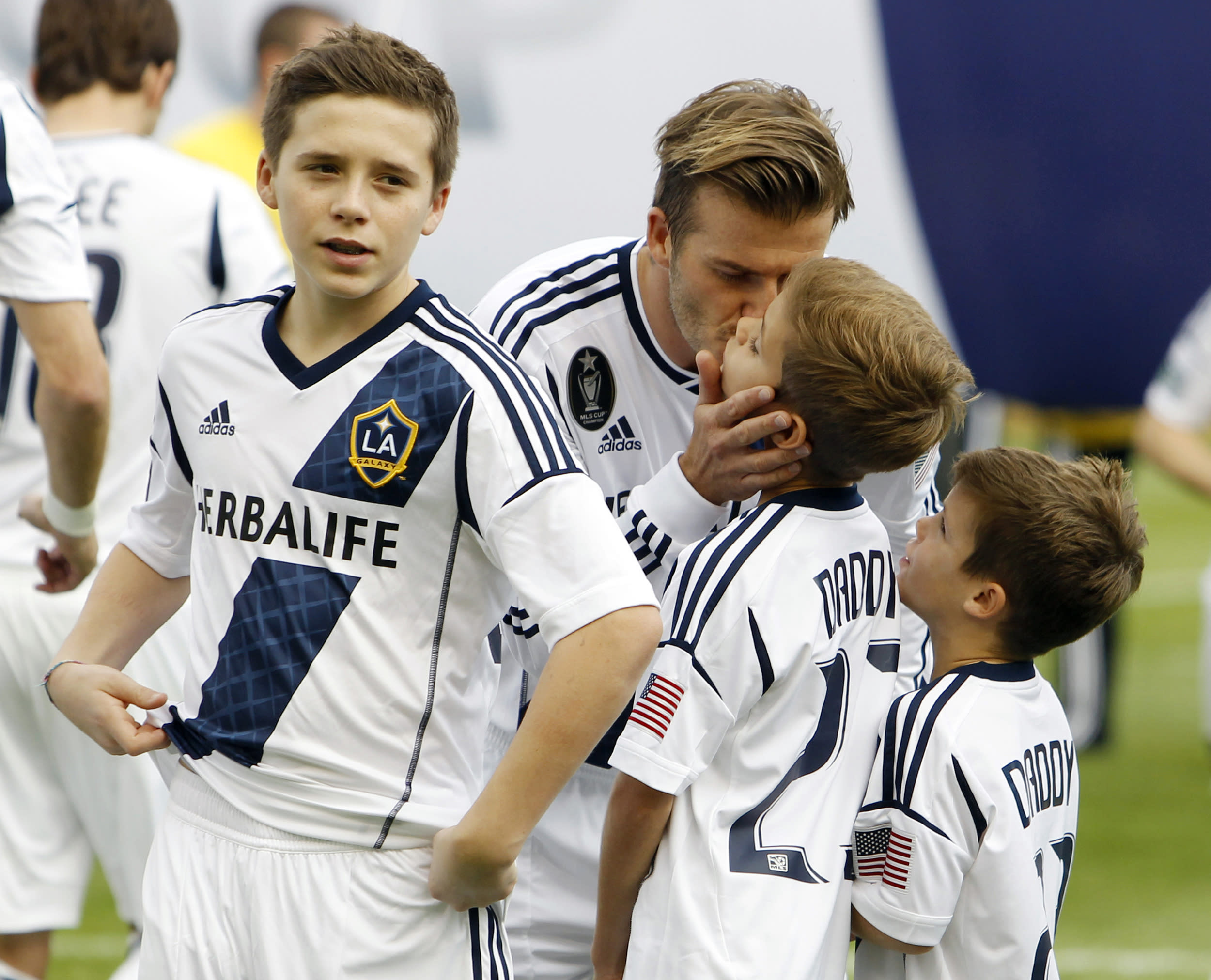 Los Angeles Galaxy's David Beckham kisses his sons Brooklyn (L), Romeo (C) and Cruz (R) before the MLS Cup championship soccer game against Houston Dynamo in Carson, California, December 1, 2012. REUTERS/Danny Moloshok (UNITED STATES - Tags: SPORT SOCCER)