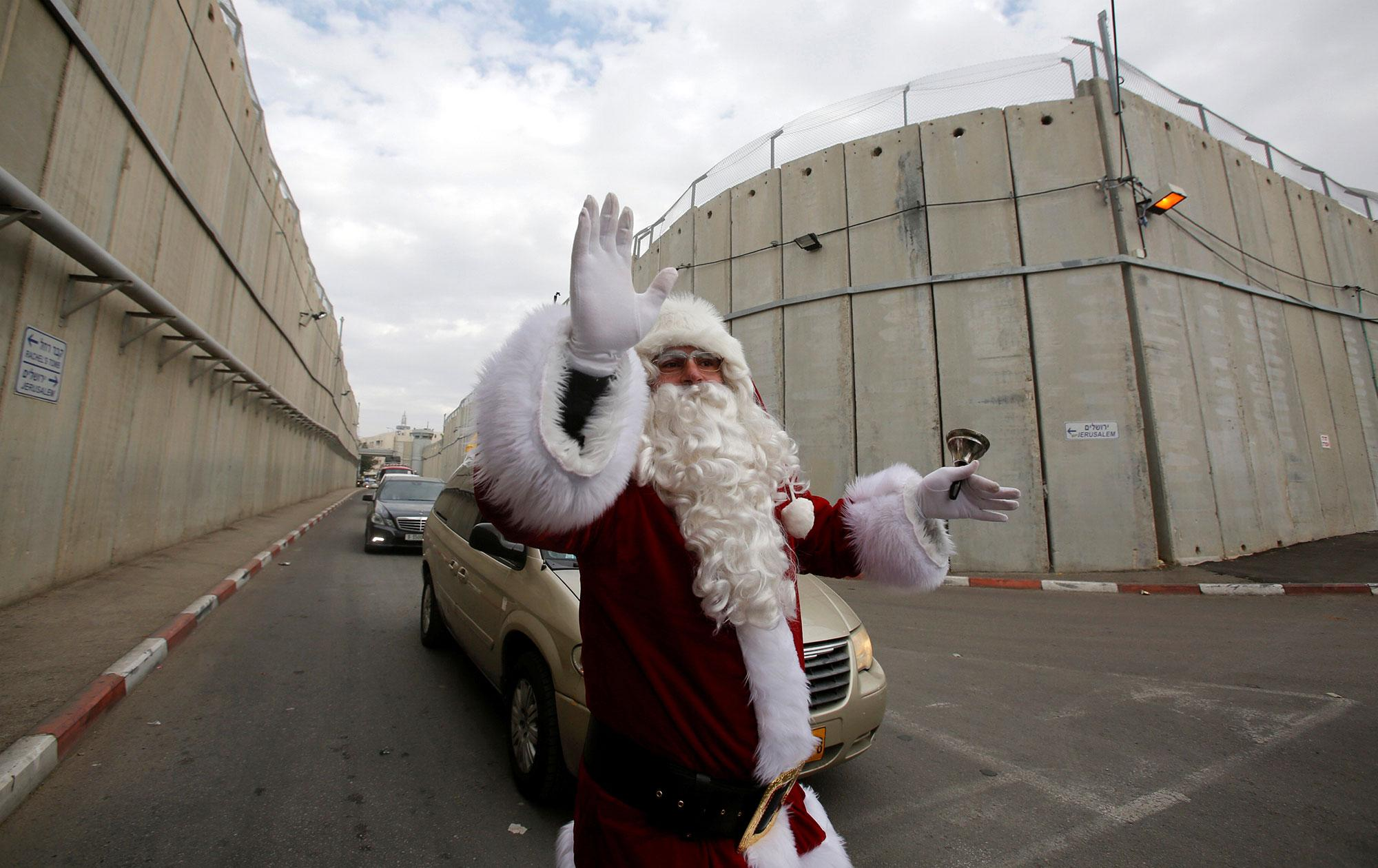 <p>A Palestinian dressed as Santa Claus gestures as the Latin Patriarch of Jerusalem Pierbattista Pizzaballa arrives through an Israeli checkpoint to attend Christmas celebrations, in the West Bank city of Bethlehem on Dec. 24, 2016. (Photo: Mussa Qawasma/Reuters) </p>