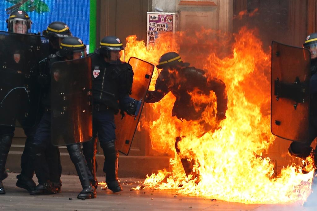 Flames engulf a French riot police officer during a demonstration against the government's controversial labour reforms in Paris on September 15, 2016 (AFP Photo/Thomas Samson)