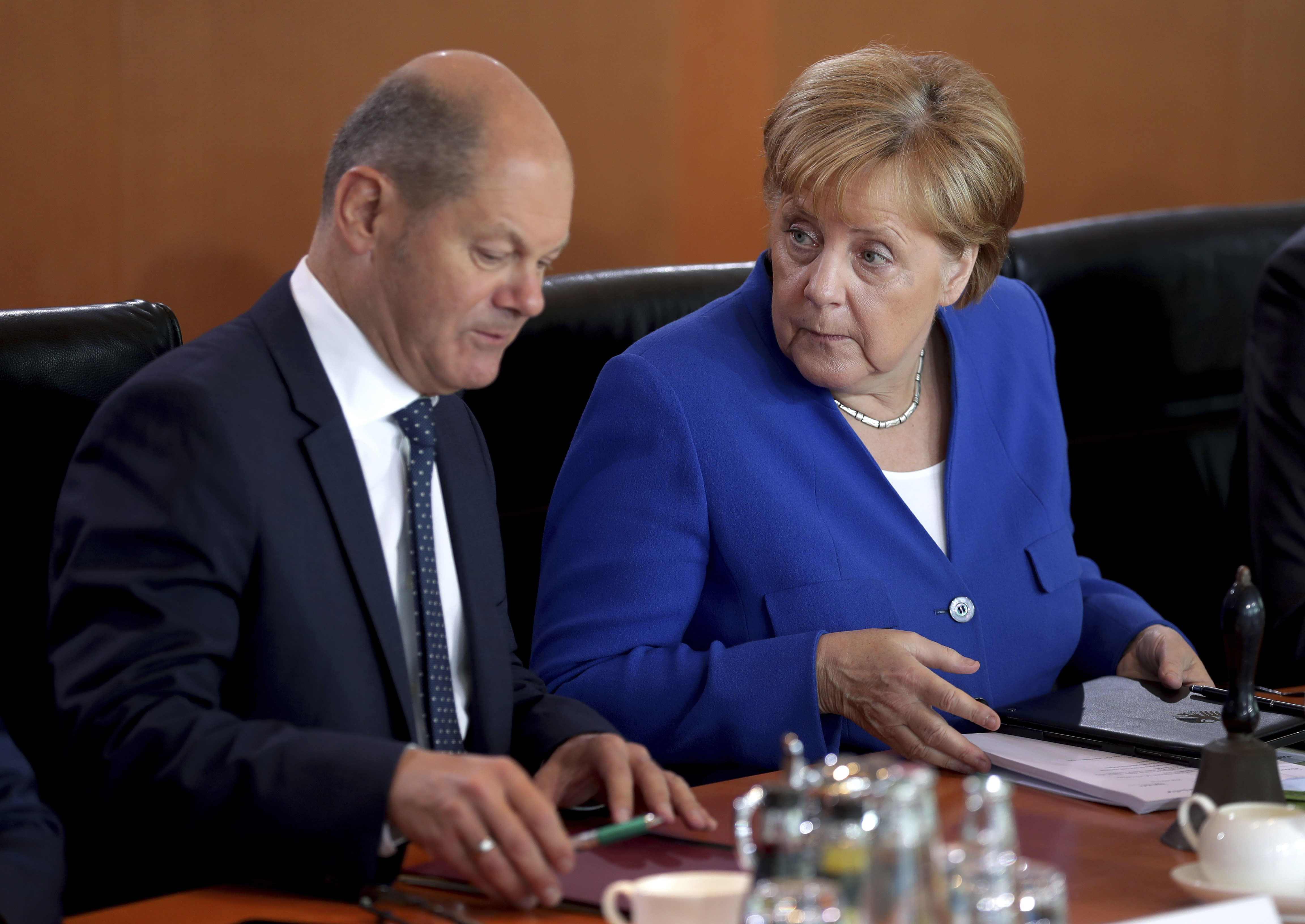 German Chancellor Angela Merkel, right, and German Finance Minister Olaf Scholz, left, talk as they arrive for the weekly cabinet meeting at the Chancellery in Berlin, Germany, Wednesday, Aug. 21, 2019. The German government sold 30-year bonds at a negative interest rate Wednesday Aug. 21, 2019, in a sign of the clouds over markets and future growth as well as increased expectations that more central bank stimulus is likely on the way.(AP Photo/Michael Sohn)