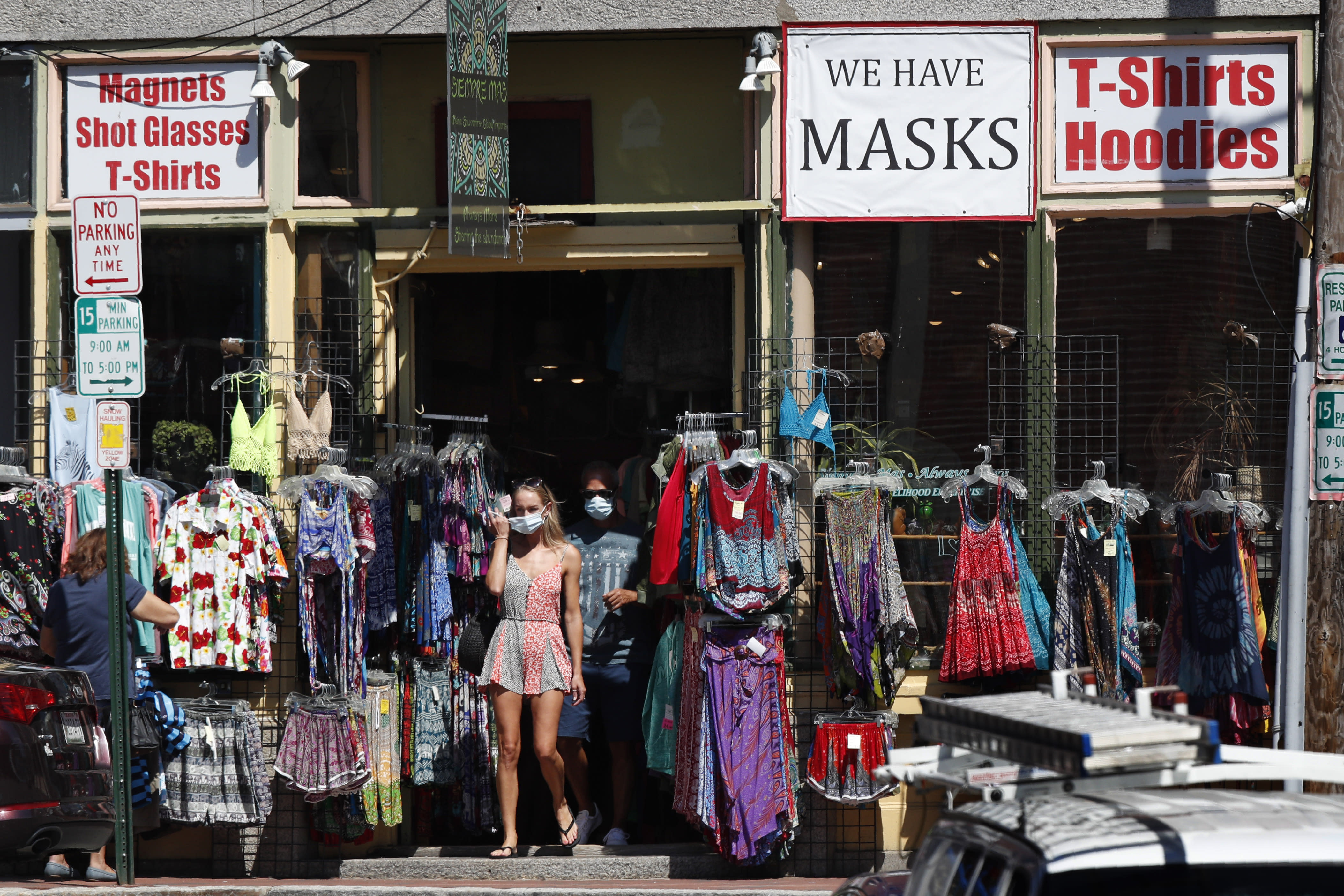 Shoppers leave a clothing shop that now also sells masks to help fight the spread of the coronavirus, Thursday, July 30, 2020, in Portland, Maine. State officials reported more cases of COVID-19. (AP Photo/Robert F. Bukaty)