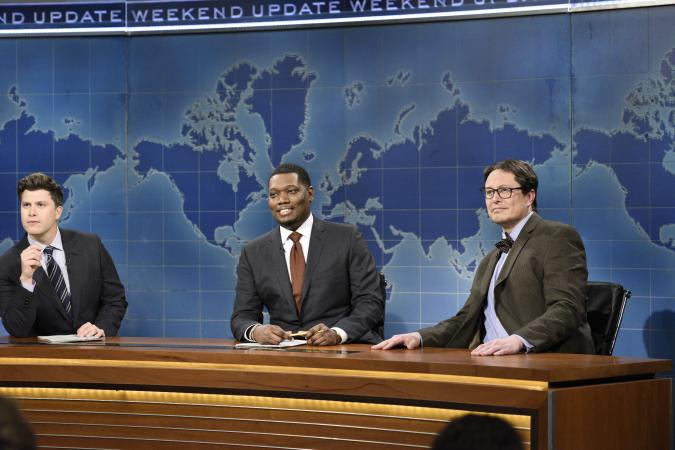 """SATURDAY NIGHT LIVE -- """"Elon Musk"""" Episode 1803 -- Pictured: (l-r) Anchor Colin Jost, anchor Michael Che, and host Elon Musk as Financial Expert Lloyd Ostertag during """"Weekend Update"""" on Saturday, May 8, 2021 -- (Photo By: Will Heath/NBC/NBCU Photo Bank via Getty Images)"""