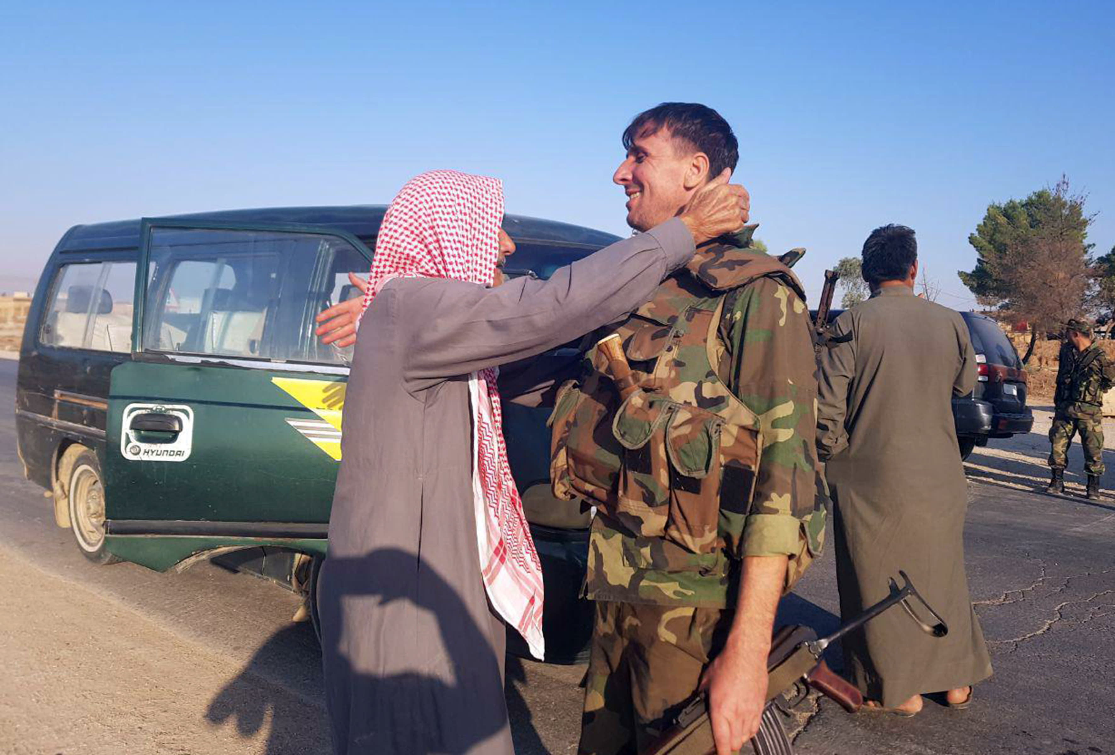 In this photo released by the Syrian official news agency SANA, a resident hugs a Syrian soldier shortly after Syrian troops entered the northern town of Tal Tamr, Monday, Oct 14, 2019. The move toward Tal Tamr came a day after Syria's Kurds said Syrian government forces agreed to help them fend off Turkey's invasion — a major shift in alliances that came after President Donald Trump ordered all U.S. troops withdrawn from the northern border area amid the rapidly deepening chaos. (SANA via AP)