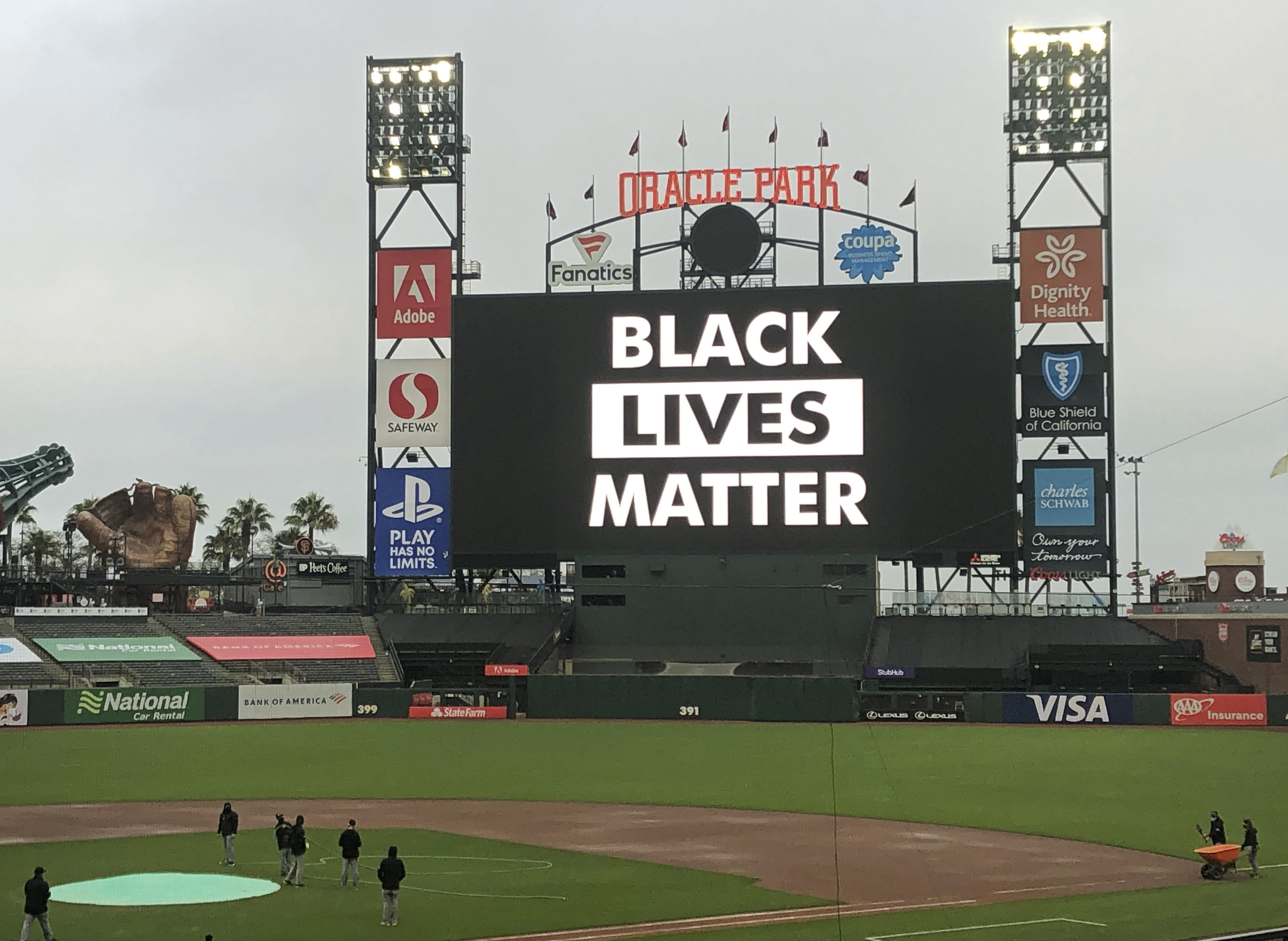 Groundskeepers work on the field as the scoreboard at Oracle Park reads Black Lives Matter at scheduled game time after a baseball game between the Los Angeles Dodgers and the San Francisco Giants was postponed on Wednesday, Aug. 26, 2020, in San Francisco. (AP Photo/Ben Margot)