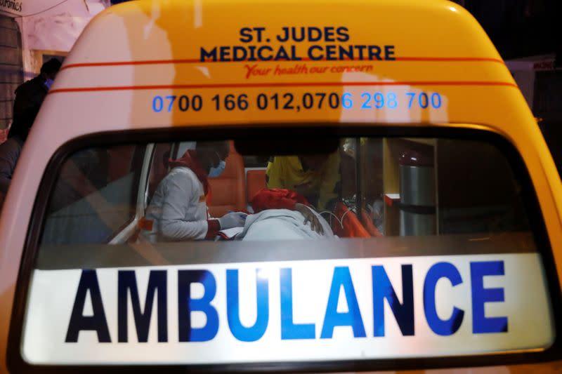 Medics examine a pregnant woman in an ambulance during the coronavirus night curfew in Nairobi
