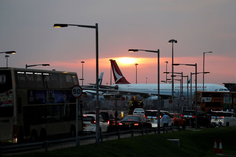 FILE PHOTO: A picture shows a traffic jam along a highway as Cathay Dragon plane is pictured at the background during an anti-extradition bill demonstration after a woman was shot in the eye in a protest in Hong Kong International Airport
