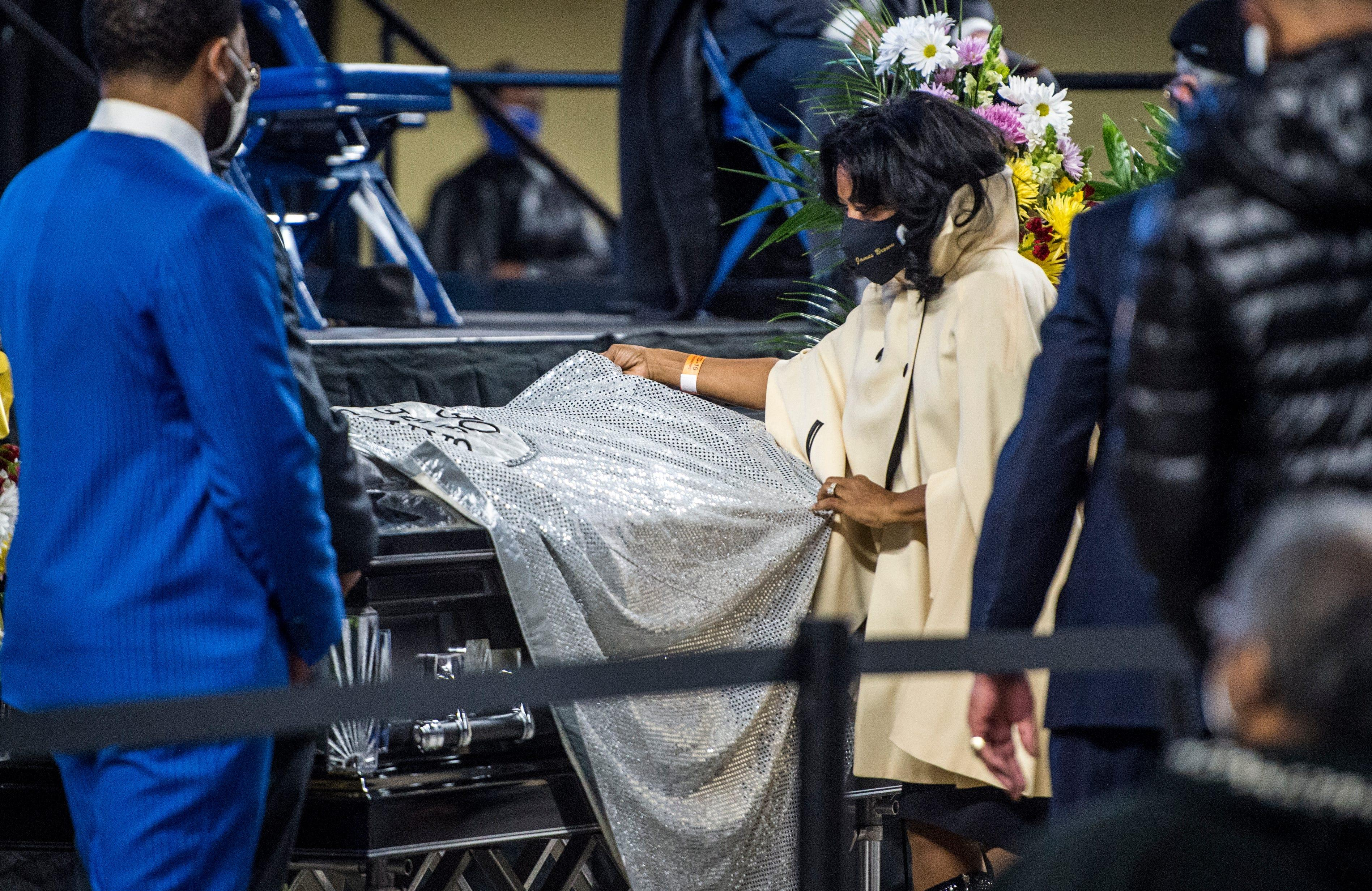 Deanna Brown-Thomas, daughter of the late soul singer James Brown, drapes one of her father's capes over the casket of Danny Ray, the famous emcee and cape man for James Brown, Saturday morning Feb. 13, 2021, at the James Brown Arena in Augusta, Ga. Ray also draped a cape over the casket of James Brown during his funeral in 2006.