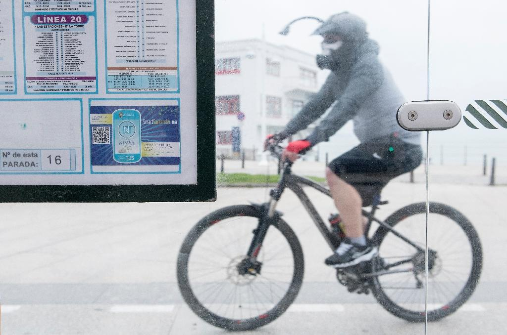 A QR code is pictured on a public bus stop as a cyclist rides past in the northern Spanish city of Santander (AFP Photo/Ander Gillenea)