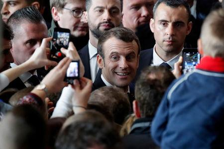Visitors Use Mobile Phones To Photograph French President Emmanuel Macron As He Visits At The International
