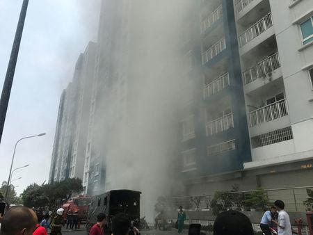 Firefighters extinguish a fire at an apartment block in Ho Chi Minh City, Vietnam March 23, 2018. VNA/Thanh Chung via REUTERS