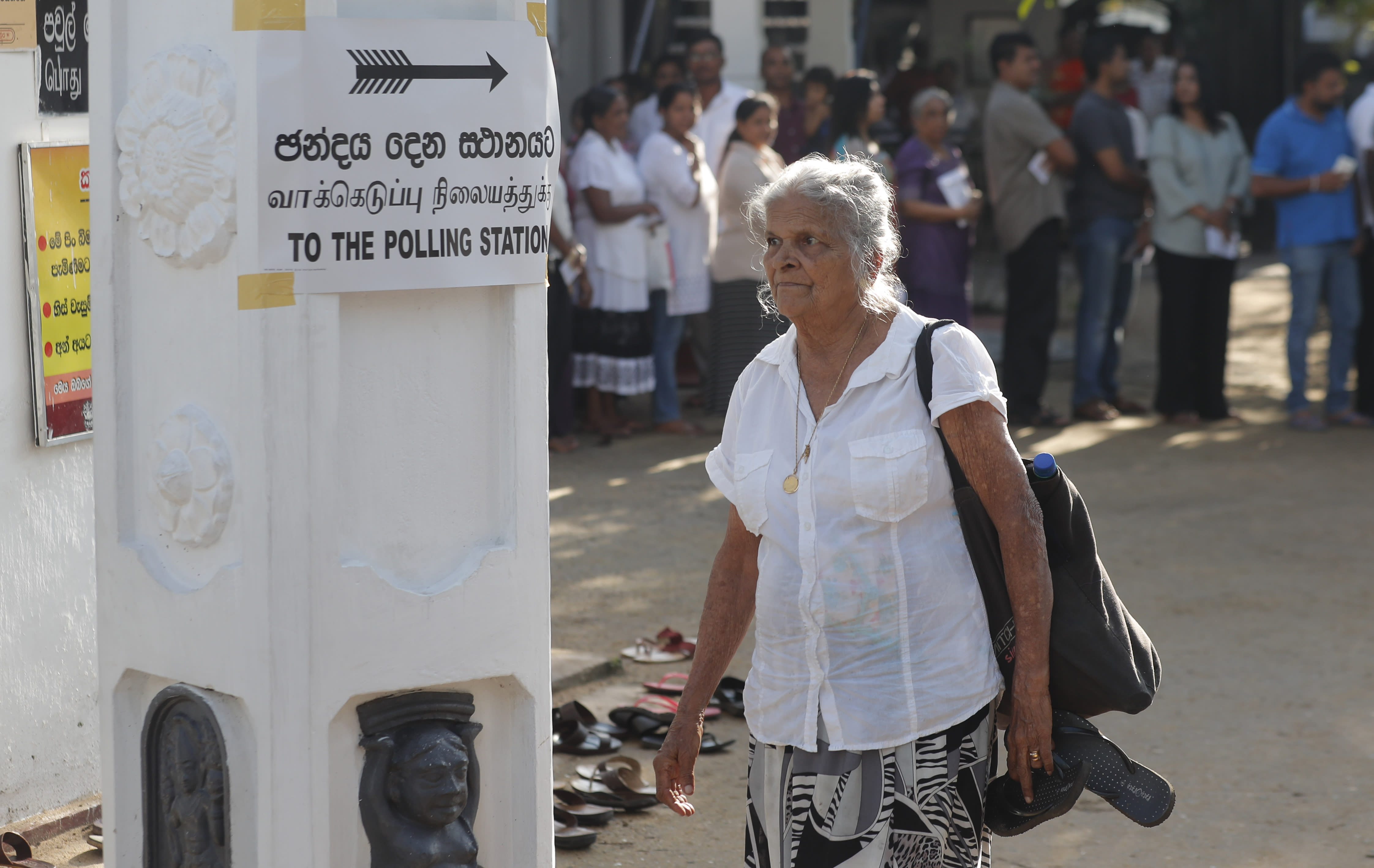 A Sri Lankan elderly woman leaves after casting her vote as others queue at a polling station during the presidential election in Colombo, Sri Lanka, Saturday, Nov. 16, 2019. Polls opened in Sri Lanka's presidential election Saturday after weeks of campaigning that largely focused on national security and religious extremism in the backdrop of the deadly Islamic State-inspired suicide bomb attacks on Easter Sunday. (AP Photo/Eranga Jayawardena)