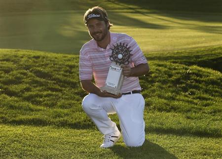 Victor Dubuisson of France poses with his trophy after his victory at the inaugural Turkish Airlines Open in the south west city of Antalya